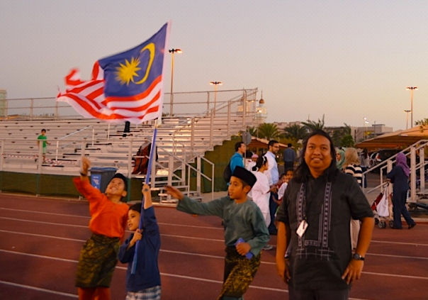 Malaysian kids cheerfully playing with their national flag